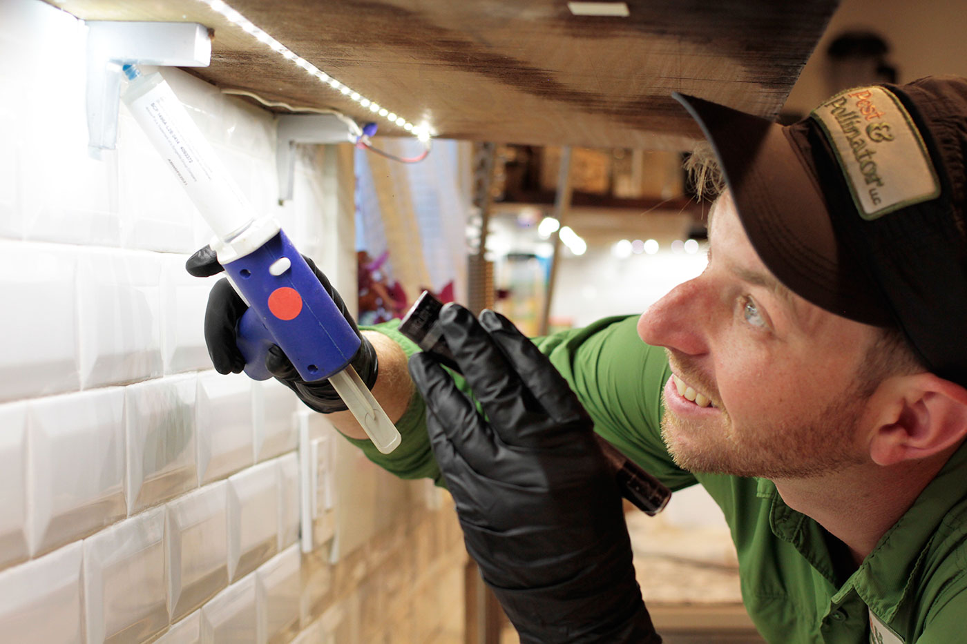 Pest control technician applying ant gel bait